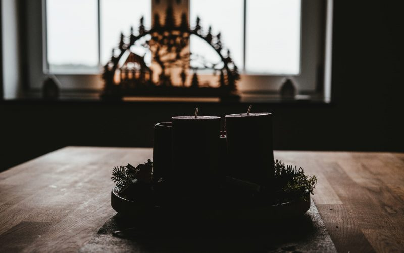 four black pillar candles on top of table